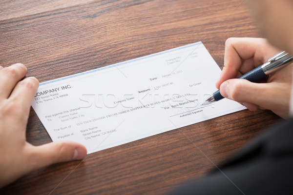 Businessman Filling Blank Cheque Stock photo © AndreyPopov
