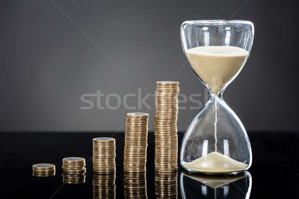 An Hourglass Near Stack Of Coins Stock photo © AndreyPopov