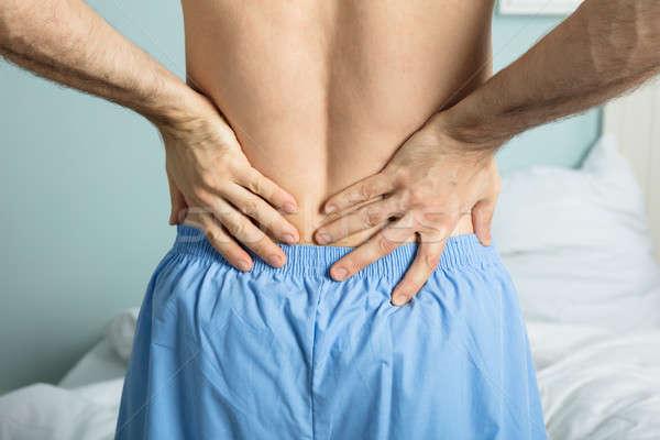 Homem dor nas costas sessão cama sofrimento Foto stock © AndreyPopov