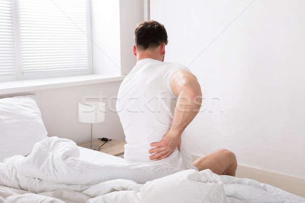 Man Sitting On Bed Having Back Pain Stock photo © AndreyPopov