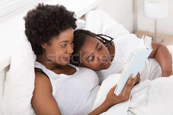 Anya gyermek olvas könyv ágy esti mese Stock fotó © AndreyPopov
