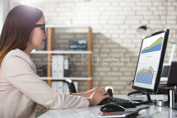 Businesswoman Analyzing Graph On Computer Stock photo © AndreyPopov
