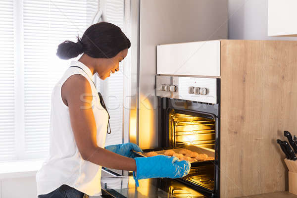 Woman Taking Out Tray Of Baked Cookies From Oven Stock photo © AndreyPopov
