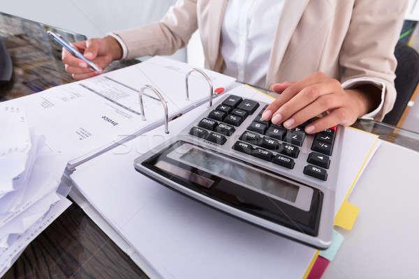 Businesswoman Hand Calculating Invoice Using Calculator Stock photo © AndreyPopov