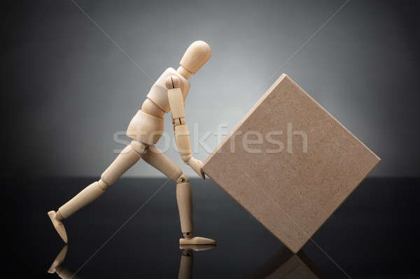 Wooden Dummy Lifting Cardboard Box Stock photo © AndreyPopov