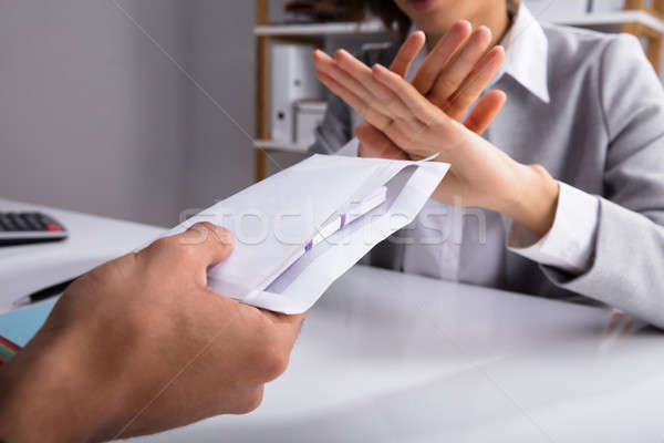 Businessperson Refusing Bribe Given By Partner In Envelope Stock photo © AndreyPopov