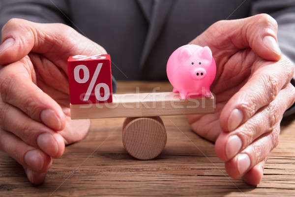 Human Hand Protecting Balance Between Percentage And Piggybank Stock photo © AndreyPopov