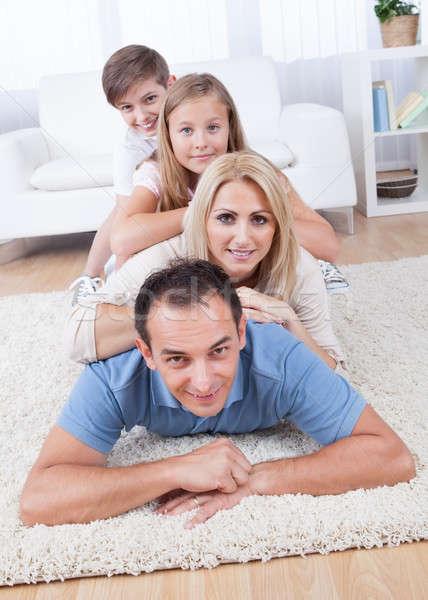 Happy Family Lying Heaped On Carpet In Living Room Stock photo © AndreyPopov
