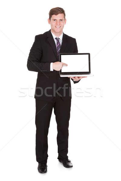 Happy businessman pointing on laptop Stock photo © AndreyPopov