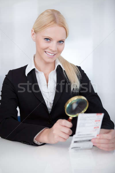 Businesswoman looking at check trough the loupe Stock photo © AndreyPopov