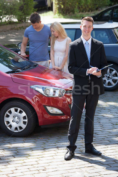 Salesman Writing On Clipboard With Couple Looking At Car Stock photo © AndreyPopov