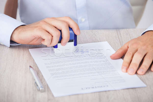Cropped Image Of Businessman Stamping Contract Paper Stock photo © AndreyPopov