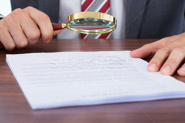 Businessman Examining Document With Magnifying Glass Stock photo © AndreyPopov