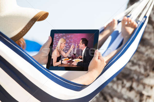 Woman Watching Movie On Digital Tablet In Hammock Stock photo © AndreyPopov