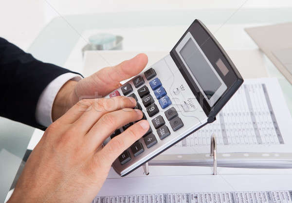 Businessman Holding Calculating Expense In Office Stock photo © AndreyPopov