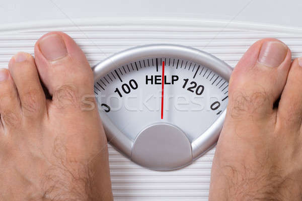 Man's Feet On Weight Scale Indicating Help Stock photo © AndreyPopov