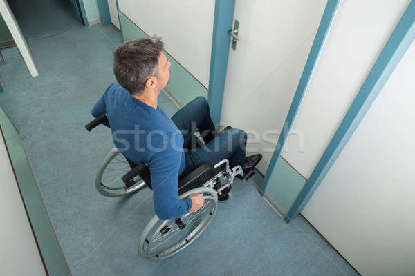 Man Sitting On Wheelchair Opening Door Stock photo © AndreyPopov