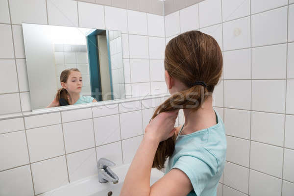 Girl Tying Hair In Bathroom Stock photo © AndreyPopov