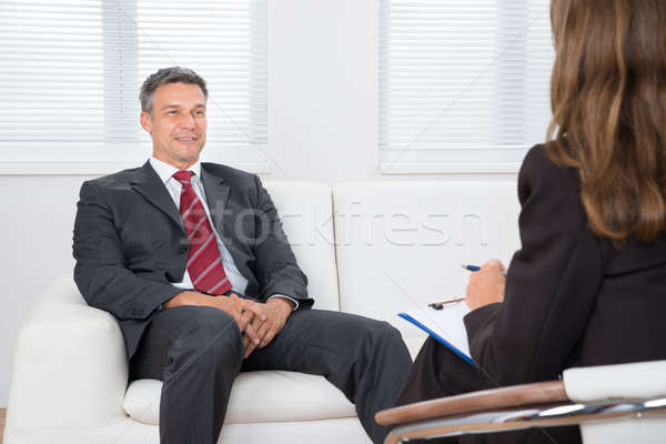 Patient On Couch In Front Of Female Psychiatrist Stock photo © AndreyPopov