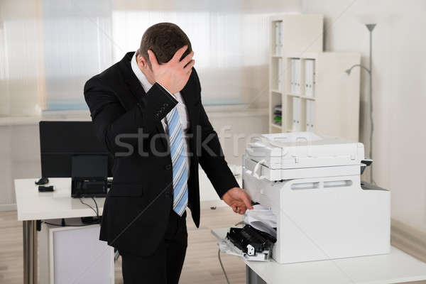 Irritated Businessman Looking At Paper Stuck In Printer Stock photo © AndreyPopov