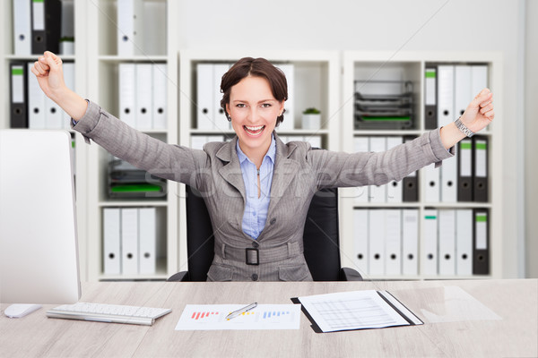 Successful Businesswoman With Arms Outstretched At Desk Stock photo © AndreyPopov
