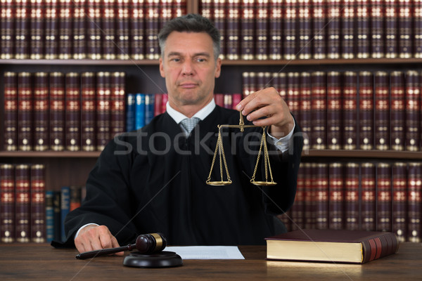 Stock photo: Judge Holding Justice Scale At Table In Courtroom