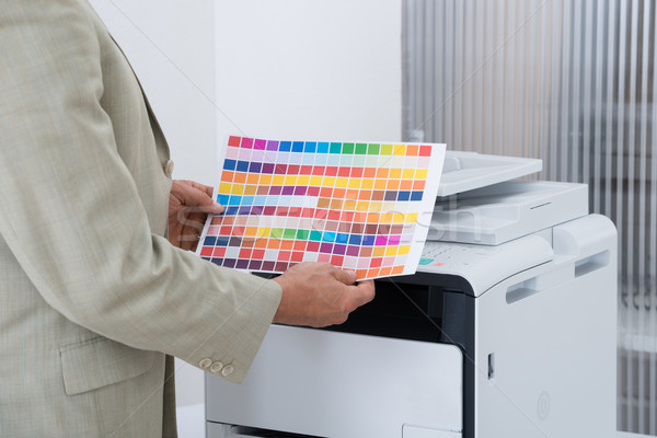 Businessman Holding Multi Colored Paper By Printer Stock photo © AndreyPopov