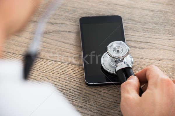 Doctor Holding Stethoscope On Smart Phone Stock photo © AndreyPopov