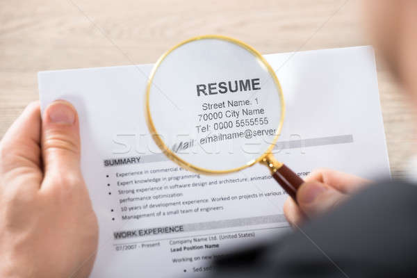 Businessman Analyzing Resume Using Magnifying Glass Stock photo © AndreyPopov