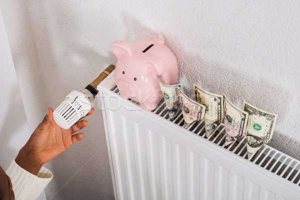 Donna termostato radiatore primo piano salvadanaio banca Foto d'archivio © AndreyPopov