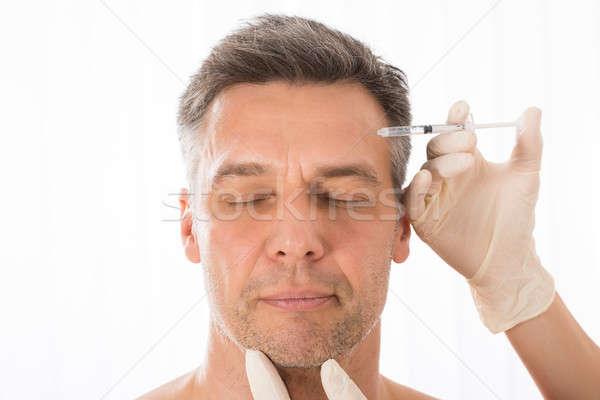 Homme mûr injection visage médecin médicaux Photo stock © AndreyPopov