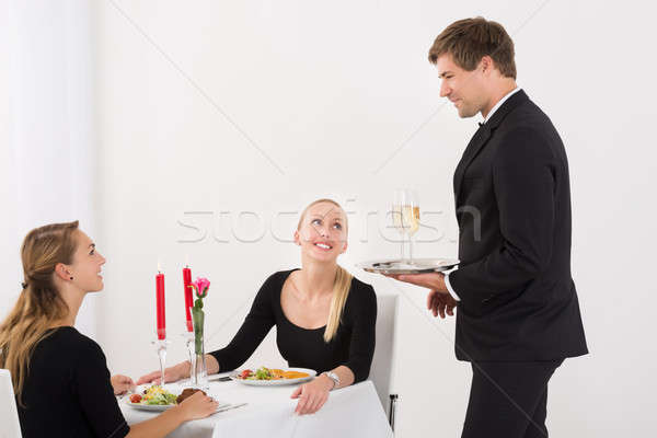 Waiter Serving Glass Of Champagne To Female Friends Stock photo © AndreyPopov