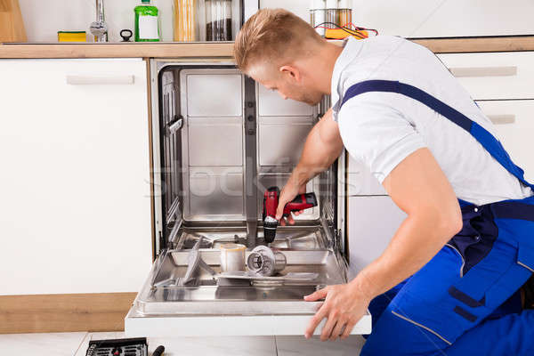 Repairman Fixing Dishwasher In Kitchen Stock photo © AndreyPopov