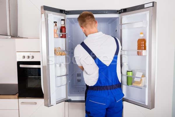 Buzdolabı genç erkek mutfak Stok fotoğraf © AndreyPopov