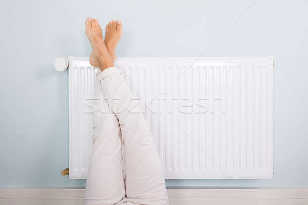 Woman Warming Up Her Feet On White Radiator Stock photo © AndreyPopov