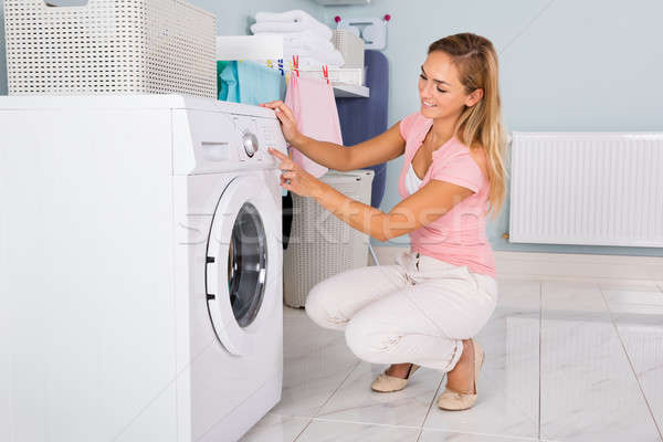 Woman Using Washing Machine In Utility Room Stock photo © AndreyPopov
