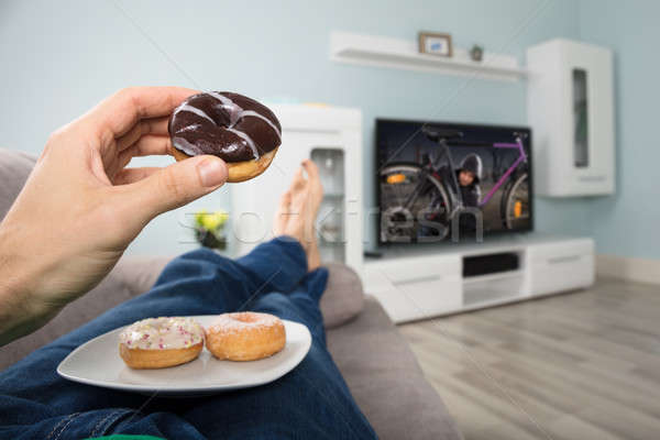 Person Eating Donut While Watching Television Stock photo © AndreyPopov