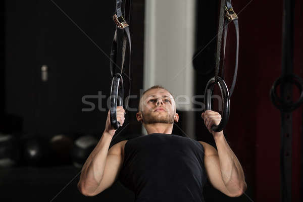 Man Exercising On Gymnastic Rings Stock photo © AndreyPopov