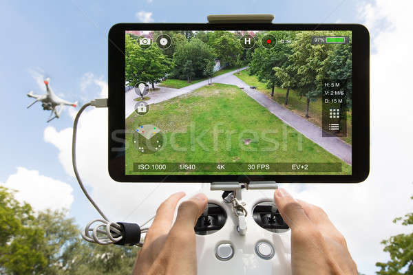 Hands controlling drone filming park against cloudy sky Stock photo © AndreyPopov