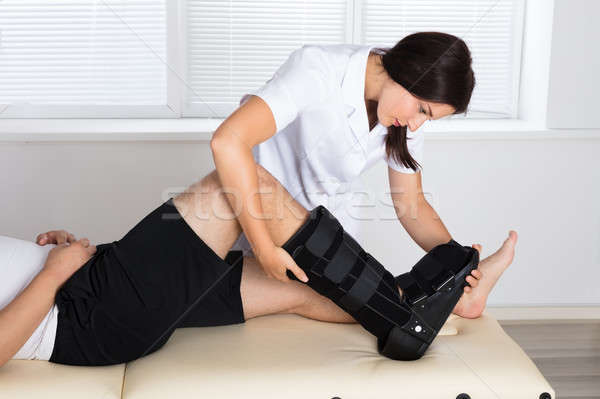 Physiotherapist Fixing Walking Brace On Patient's Leg Stock photo © AndreyPopov