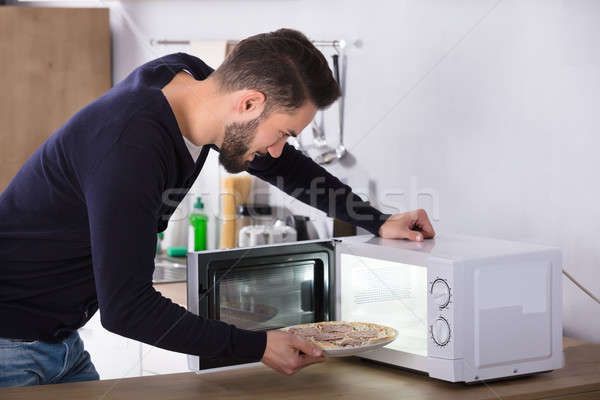 Man Baking Pizza In Microwave Oven Stock photo © AndreyPopov
