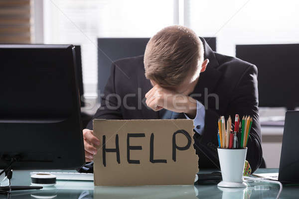 Businessman Holding Cardboard With Help Text Stock photo © AndreyPopov