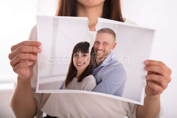 Woman Tearing Photo Of Happy Couple Stock photo © AndreyPopov