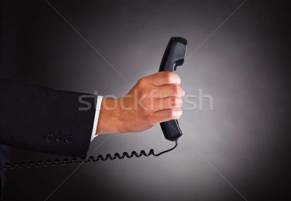 Hand Holding Telephone Receiver Over Black Background Stock photo © AndreyPopov