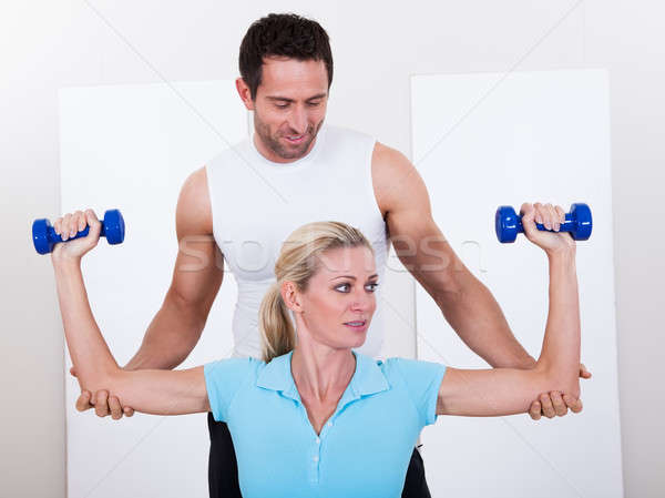 Fitness instructor helping a woman workout Stock photo © AndreyPopov
