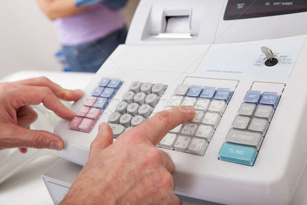 Sales person entering amount on cash register Stock photo © AndreyPopov