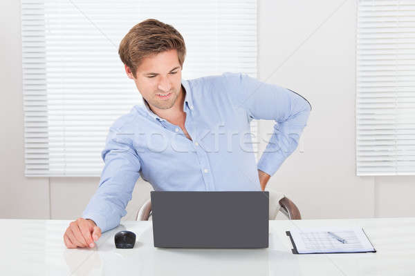 Businessman Suffering From Backache While Working On Laptop Stock photo © AndreyPopov