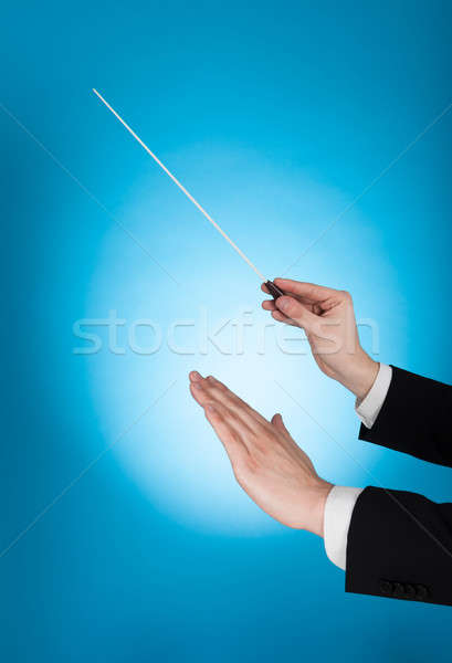Musician Holding Baton Against Blue Background Stock photo © AndreyPopov