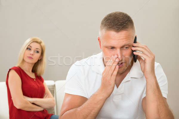 Wife Looking At Husband Talking On Mobile Phone Stock photo © AndreyPopov