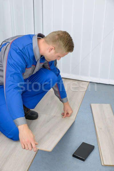 Stock photo: Worker Assembling New Laminate Floor